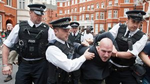 A protester is arrested outside the Ecuador Embassy in London